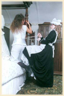 A maid fastens her mistresses corset.